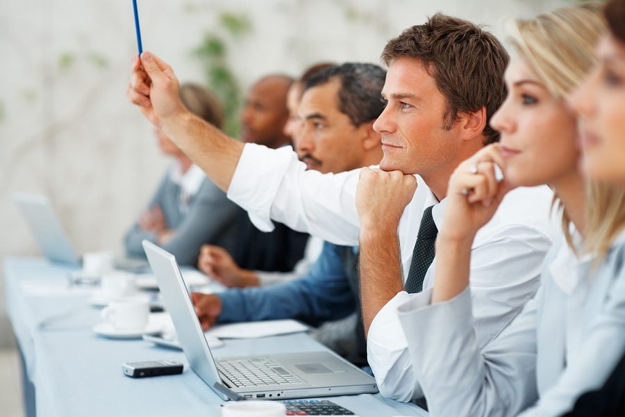 Focus on business man with hand raised during meeting
